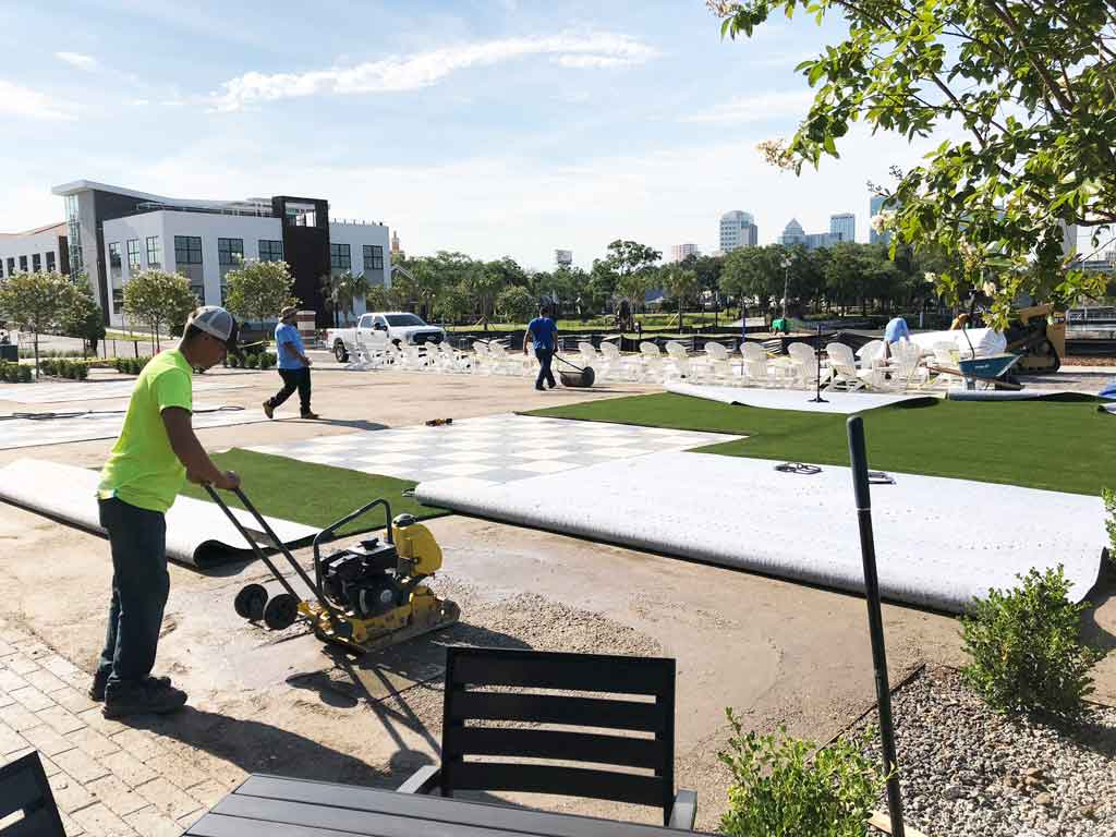 ForeverLawn Tampa Bay workers installing artificial grass at Armature Works