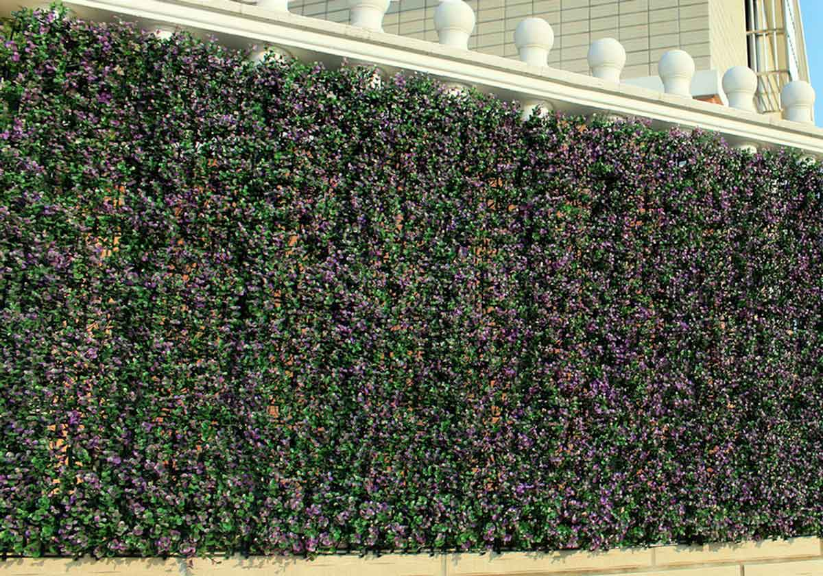a wall of tall artificial hedges by NatraHedge